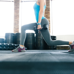 Closeup image of a woman working out with dumbbells at gym